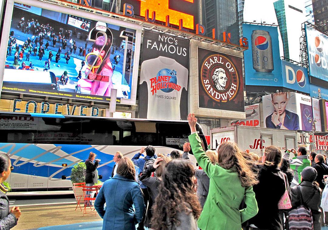 在纽约时代广场上,人们正在 Forever 21 广告牌前看自己的影子